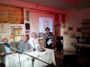 Η κ. Καίτη Βλαχογιάννη, κόρη του Ντίνου Βλαχογιάννη, διαβάζει το ευχαριστήριο του πατέρα της κατά τη βράβευσή του απο το δήμο Κορίνθου. Καθιστοί δίπλα της ο Λεωνίδας Στεργιόπουλος και ο Κώστας Βασιλείου.